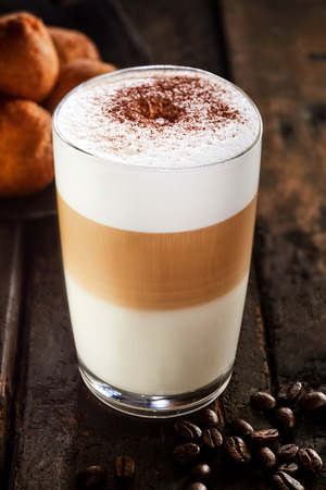 Glass of latte macchiato scattered with cocoa standing on wooden table