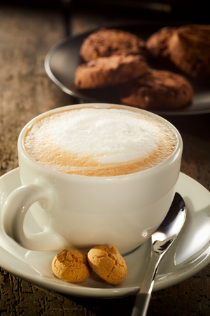 Freshly brewed cup of cafe latte coffee served with two small macaroons and a plate of cookies in a rustic restaurant Stock Photo