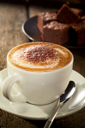 Appetizing cup of hot frothy cappuccino topped with cocoa powder served in a cup with chocolate cake in the background