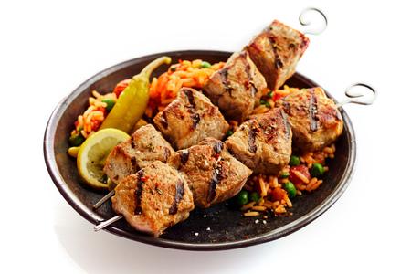 Disparo de primer plano de estudio de carne a la parrilla en dos pinchos con guarnición de una mezcla de arroz y verduras servido en plato sobre fondo blanco