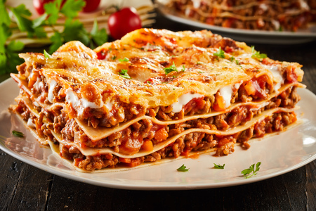 Portion of succulent ground beef lasagne topped with melted cheese and garnished with fresh parsley served on a plate in a close up view for a menu Standard-Bild