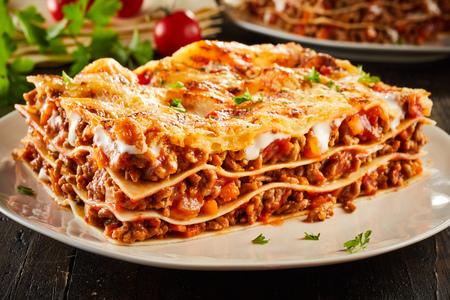 Gedeelte sappige rundergeharde lasagne gegarneerd met gesmolten kaas en gegarneerd met verse peterselie geserveerd op een bord in een close-up voor een menu