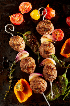 Roasted meatballs with peppers, garlic, tomatoes against dark background