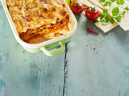 Tasty lasagne topped with grated cheese on wooden table with fresh tomatoes Reklamní fotografie - 88622910
