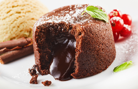 Close up view of chocolate lava cake with ice cream on plate
