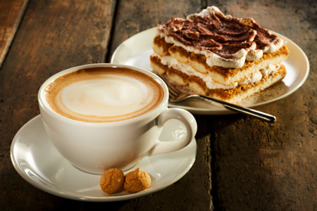 Cup of double espresso coffee with piece of cake on wooden table