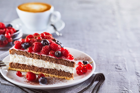 Piece of layered creamy fruit cake with raspberries and blackberries against cup of coffee