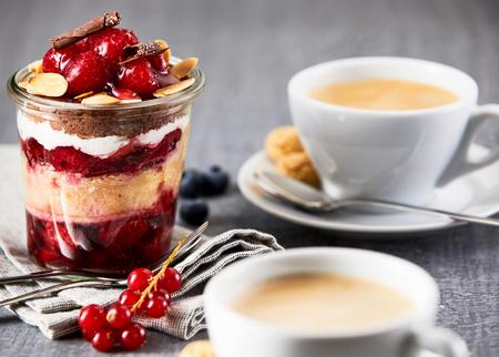 Gelaagd fruitdessert in kruik onder koppen van koffie op lijst Stockfoto