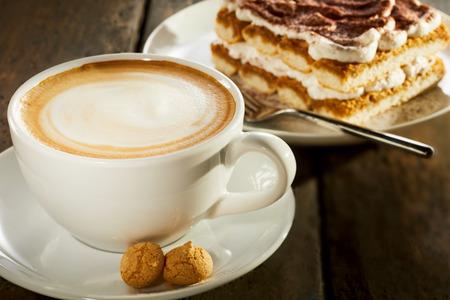 근접에서 테이블에 케이크의 조각으로 우유 커피 한잔