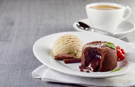 Chocolade lava cake met ijs geserveerd op plaat tegen kopje koffie