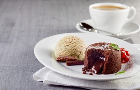 Chocolate lava cake with ice cream served on plate against cup of coffee