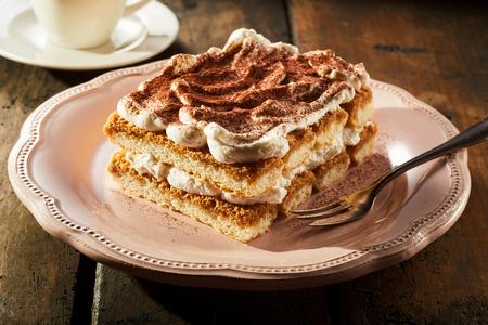 Piece of mouth-watering layered tiramisu cake with cream on plate
