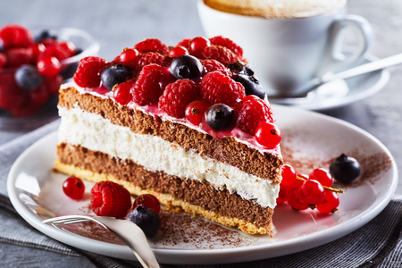 Slice of gourmet fresh berry cake on a plate with layered cream topped with fresh autumn raspberries, blueberries and redcurrants in a close up view on a plate 스톡 콘텐츠