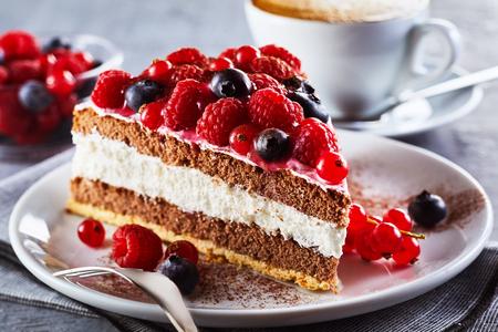 Fetta di torta di bacche fresche gourmet su un piatto con crema a strati condita con lamponi freschi di autunno, mirtilli e ribes rosso in una vista da vicino su un piatto