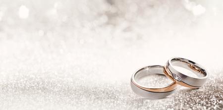Los anillos de boda de diseño en la esquina sobre un fondo brillante de brillo en formato de banner panorámico con espacio de copia y enfoque selectivo Foto de archivo