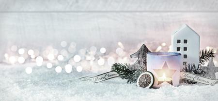 Banner di panorama festivo di Natale Merry invernale con una disposizione decorativa di pigne e rami con una candela accesa e cottage in neve bianca fresca contro un bokeh scintillante di luci di partito Archivio Fotografico