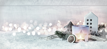Wintry Merry Christmas festive panorama banner with a decorative arrangement of pine cones and branches with a burning candle and cottage in fresh white snow against a sparkling bokeh of party lights Stockfoto