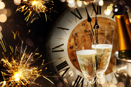 Festive New Years background with sparklers and champagne in front of a clock counting down to midnight with sparkling bokeh on darkness