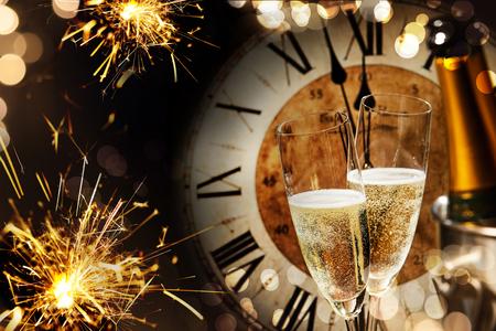 Fondo festivo de año nuevo con luces de Bengala y champán frente a un reloj de cuenta regresiva hasta la medianoche con un chispeante bokeh en la oscuridad