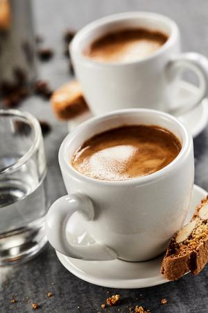 Nahaufnahme von Tassen doppelter Espresso mit Glas Wasser