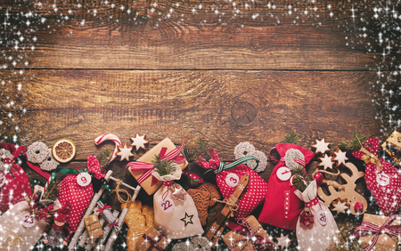 Festive Christmas border with advent calendar composed of little bags tied as gifts with the date in a still life with Xmas ornaments on rustic wood with copy space Stock Photo