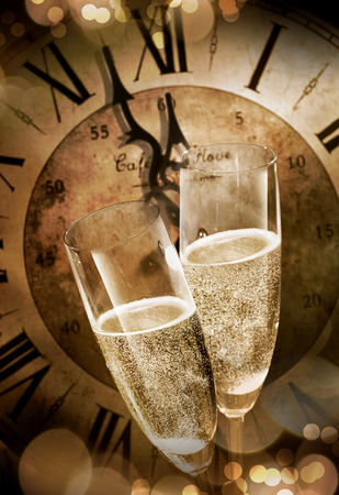 Close-up of two champagne flutes toasting before midnight against a vintage clock during romantic celebration at New Years Eve Stock Photo