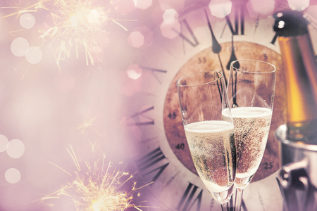 Happy New Year background or card for celebrating with champagne flutes and fireworks against a vintage clock at midnight party Stock Photo