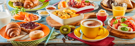 Colorful breakfast spread in a panoramic banner with smoked salmon, Caprese salad, scrambled and boiled egg, meat cheese donut, toast and jam, orange juice and coffee viewed low angle