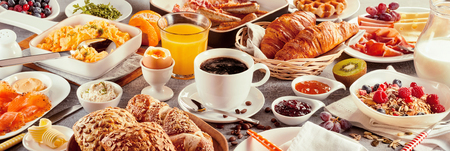 Morning breakfast banner with a coffee cup served surrounded by various nutritious food as delicious French croissants, cereals, and fruits