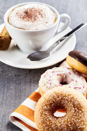 Assorted donuts and a cup of freshly brewed frothy cappuccino coffee served for a tasty breakfast or coffee break Stock Photo