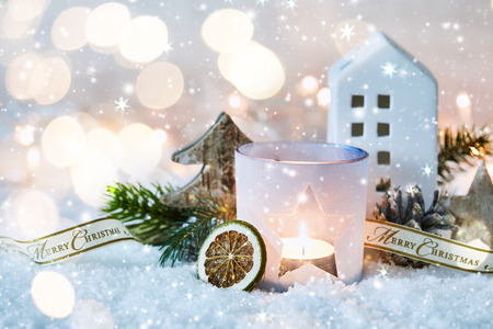 Christmas decorative winter background with a glowing candle and falling snow over pine foliage and cones with a small cottage and sparkling bokeh of party lights