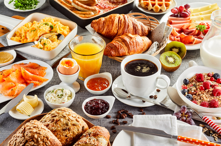 Enorm, gezond ontbijt verspreid op een tafel met koffie, sinaasappelsap, fruit, muesli, gerookte zalm, eieren, croissants, vlees en kaas