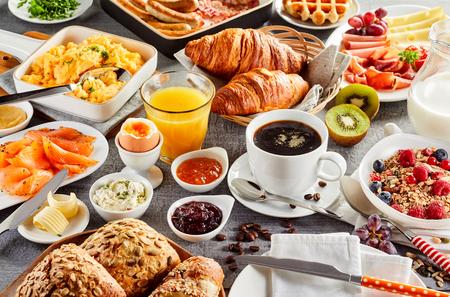 Enorme desayuno saludable que se extiende sobre una mesa con café, jugo de naranja, fruta, muesli, salmón ahumado, huevo, croissants, carne y queso.