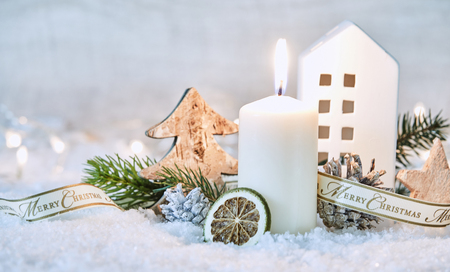 Merry Christmas winter still life with fresh white snow, pine cones and foliage and a burning candle in front of a cottage