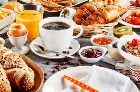 Alimenti per la colazione del mattino con pane, caffè, uova, succo sul tavolo Archivio Fotografico - 90000844
