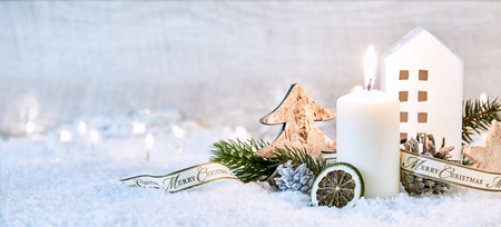 Festive white winter Christmas panoramic banner with a glowing candle amongst decorative ornaments in snow with a sparkling bokeh of party lights and copy space behind Stock Photo