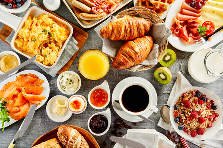 Large selection of breakfast food on a table with muesli , eggs, croissant, orange juice, fruit, smoked salmon, cold meats, cheese and jam served with coffee viewed from above 스톡 콘텐츠