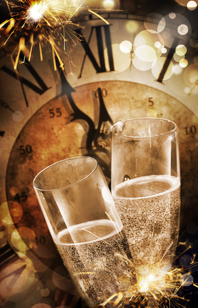 Close-up of two champagne flutes toasting against a vintage clock before midnight during party with fireworks for celebrating New Year Foto de archivo