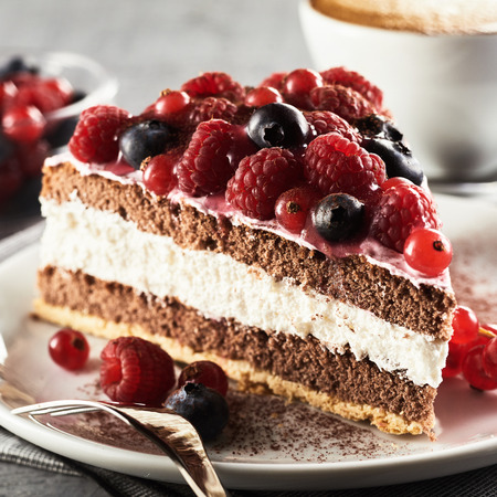 Close up view of layered creamy fruit cake with berries served on plate