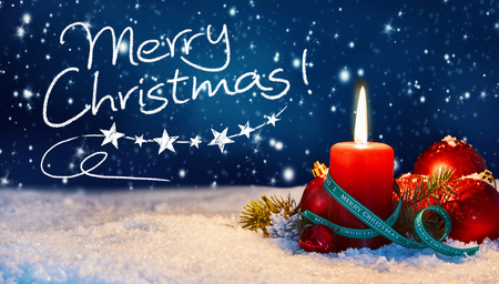 Festive Merry Christmas greeting background with handwritten text on a twilight sky with snowflakes and a burning candle in snow surrounded by red baubles