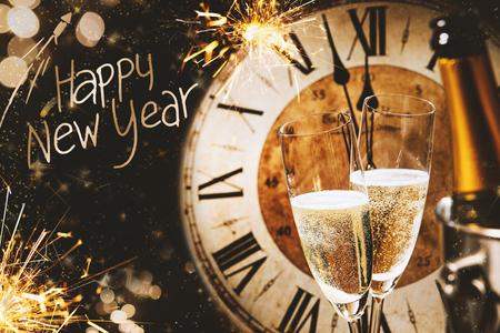 Biglietto di auguri di felice anno nuovo con champagne di fronte a un orologio che conta fino a mezzanotte e un bokeh scintillante di luci e stelle filanti Archivio Fotografico - 89782906