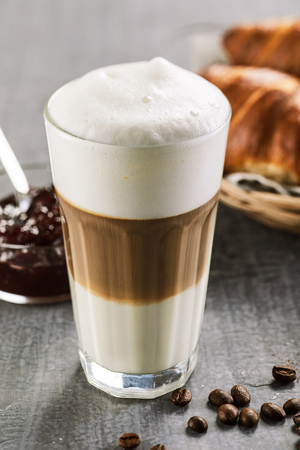 Glass of macchiato coffee with thick milk foam standing on table in close up view Stock Photo