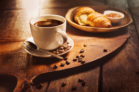 Cup of coffee with croissant on wooden board in background