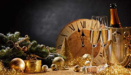 フルートと各種ゴールド季節休日の装飾上の深夜のコピー スペースまでカウント ダウン時計の前でシャンパンのボトルと広角新年バナー