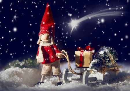 Decorative Christmas doll pulling a sled with gifts through winter snow under a starry sky with a shooting star leading the way to Bethlehem symbolic of the Wise Men Stock Photo