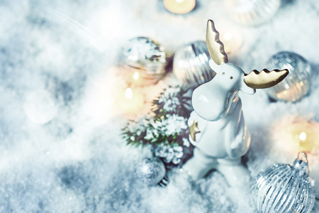Adorable little white Christmas reindeer in snow surrounded by baubles, fir and burning twinkling candles viewed from above with copy space