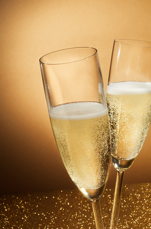 Two romantic flutes of sparkling champagne on a glitter background conceptual of a party celebration for an anniversary, wedding, New Year or Valentines Day
