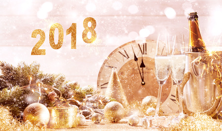 2018 festive gold background with two flutes of sparkling champagne in front of a clock counting down to midnight and assorted festive holiday decorations