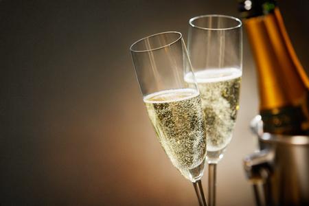 Zwei romantische Gläser funkelnder Champagner neben einer Flasche in einem Eiseimer- und Kopienraum, um eine Hochzeit, einen Jahrestag, ein neues Jahr oder einen Valentinstag zu feiern