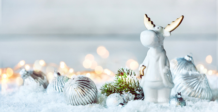 Cute little white Christmas reindeer in winter snow with silver baubles and fir foliage in a panorama banner with copy space Stock fotó